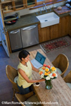 Picture of a Native American woman arranging a bouquet of roses on the counter in her kitchen - Stock Photos